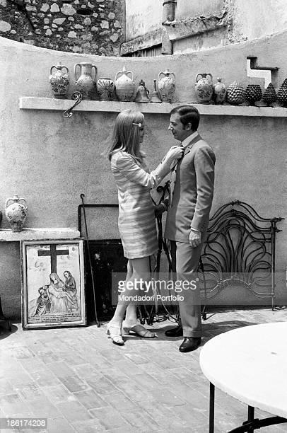 Italian journalist and art director Annarita Torsello tidying the tie of her partner the Italian TV and radio presenter Mike Bongiorno Taormina May...