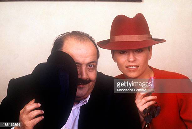 Italian journalist and TV host Maurizio Costanzo hiding himself behind a hat beside his wife and Italian TV presenter Maria De Filippi holding a rose...