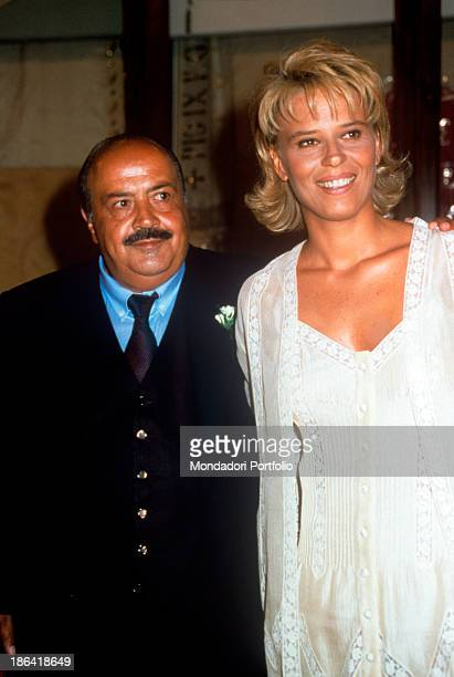 Italian journalist and TV host Maurizio Costanzo hugging his smiling wife and Italian TV presenter Maria De Filippi 1995