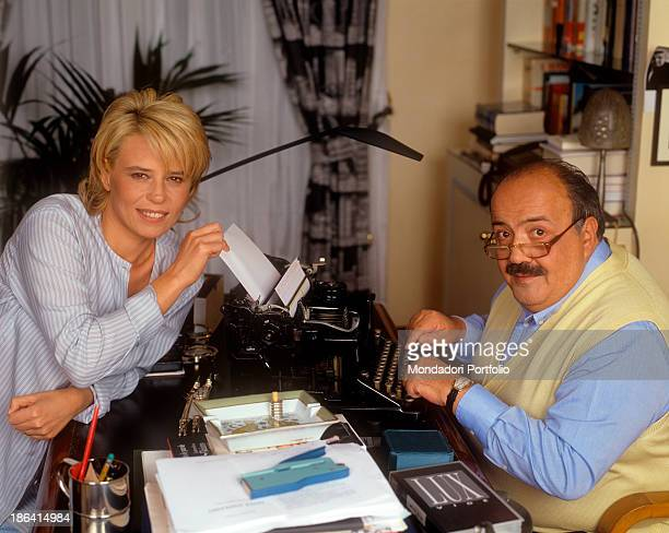Italian journalist and TV host Maurizio Costanzo sitting in front of a typewriter beside his wife and Italian TV presenter Maria De Filippi. 1995.