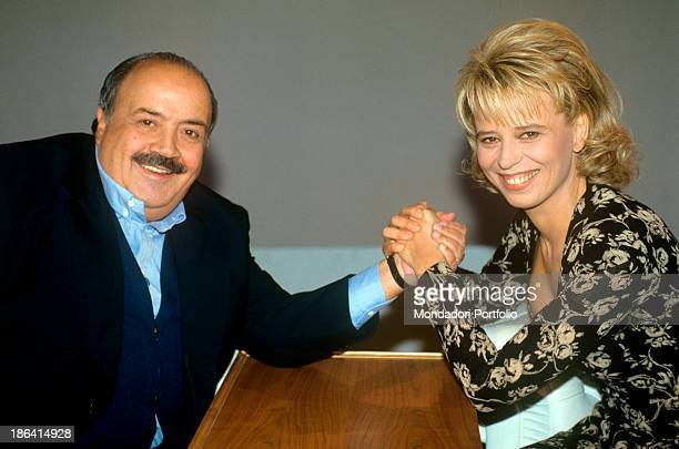 Italian journalist and TV host Maurizio Costanzo smiling holding his wife and Italian Tv presenter Maria De Filippi by the hand. 1995.