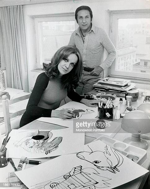Italian journalist Annarita Torsello drawing at the desk Her husband the Americanborn Italian TV host Mike Bongiorno smiling behind her Milan April...