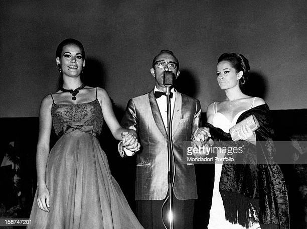 Italian journalist Lello Bersani shaking hands with French actress Claudine Auger and Italian actress Luciana Paluzzi 1965