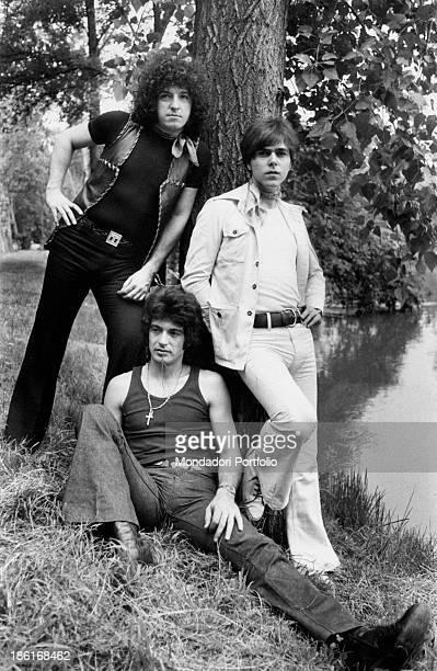 Italian keyboard player Gabriele Lorenzi sitting on the grass leaning on a tree between Italian guitarist and singer Alberto Radius and Italian...