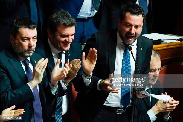 Italian Lega party far-right leader Matteo Salvini , supported by Lega member Gian Marco Centinaio , reacts as he addresses the Senate on February...