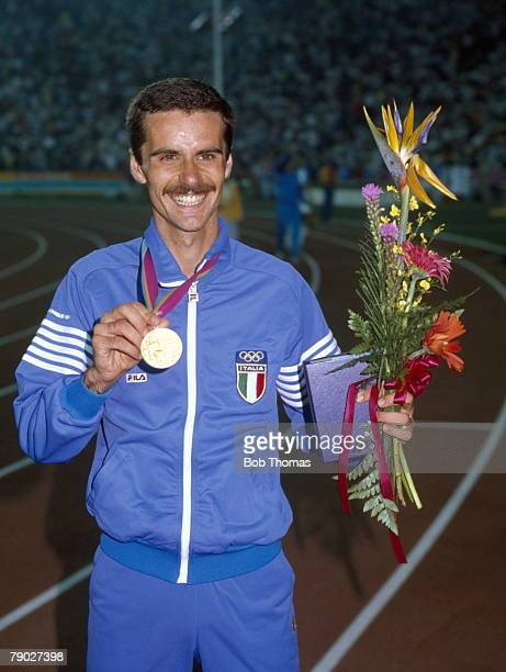Italian long distance track athlete Alberto Cova proudly displays his gold medal after coming first in the final of the Men's 10000 metres event at...