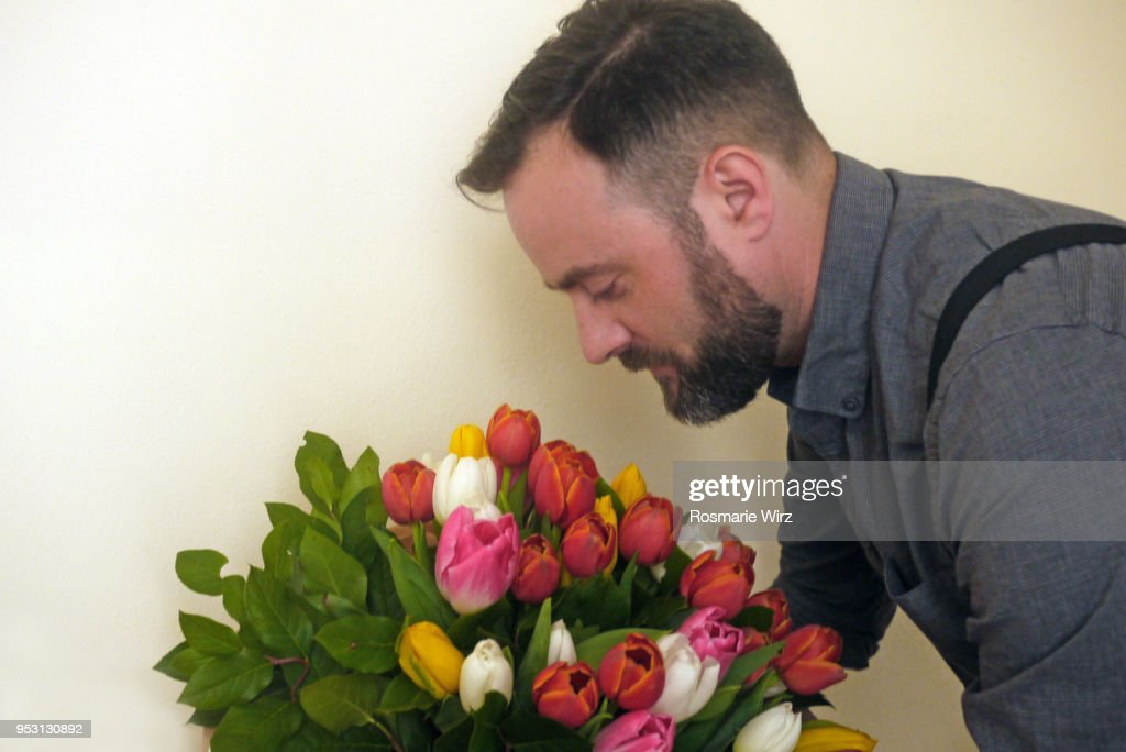 Italian man in profile looking at tulip flower arrangement : ストックフォト
