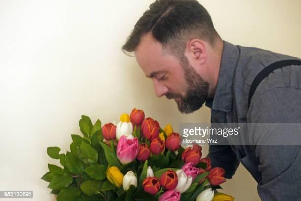 italian man in profile looking at tulip flower arrangement - 40歳の誕生日 ストックフォトと画像