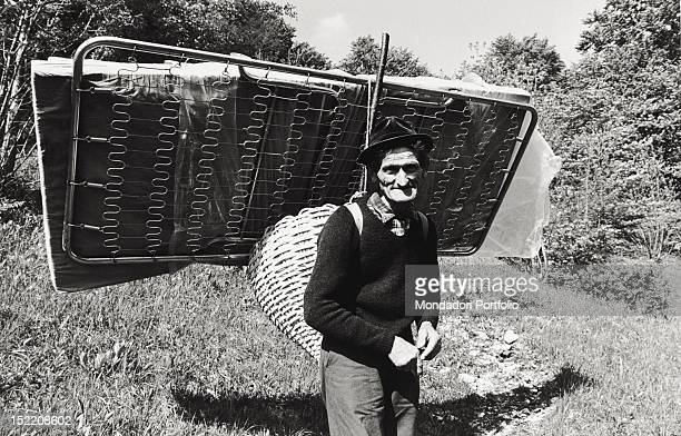 Italian man left homeless by the Friuli earthquake carrying on his back his bed rescued from the debris of his house FriuliVenezia Giulia May 1976