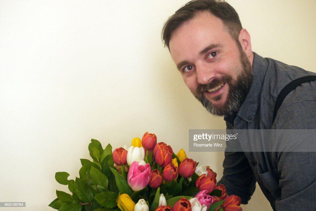 Italian man smiling at camera with tulip flower arrangement : ストックフォト