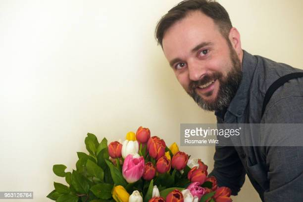 italian man smiling at camera with tulip flower arrangement - 40歳の誕生日 ストックフォトと画像