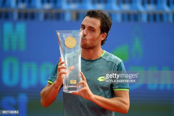 Italian Marco Cecchinato kisses the trophy after his victory over Australian John Millman at the end of their ATP final tennis match at the Hungarian...