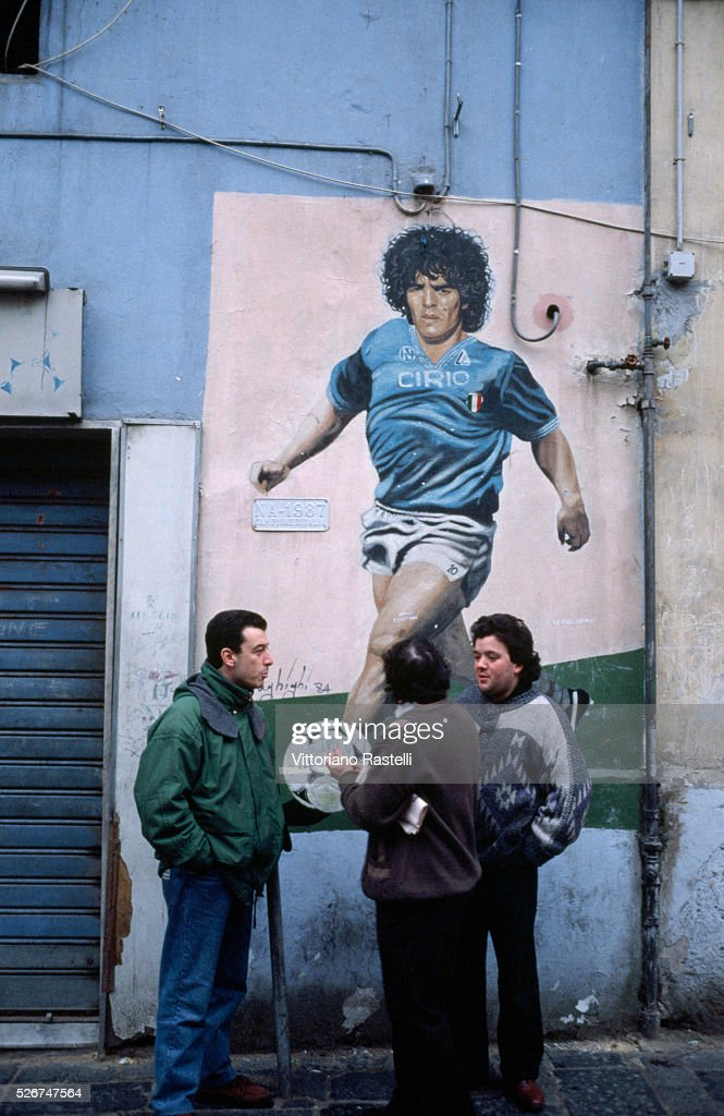 Italian men stand near a mural of footballer Diego Maradona on a street in Naples.