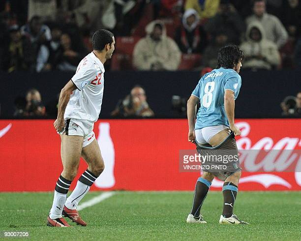 Italian midfielder Gennaro Gattuso fixes his short next to Egytpian forward Mohamed Aboutrika during the Fifa Confederations Cup football match Egypt...