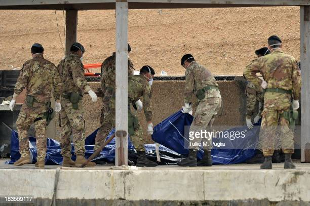 Italian military personnel disembark from a boat carrying the bodies of African migrants killed in a shipwreck off the Italian coast lie in Lampedusa...