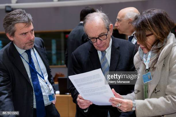 Italian Minister Economy Finance Pier Carlo Padoan is looking at papers with staff members prior an EcoFin Ministers meeting on December 5 2017 in...