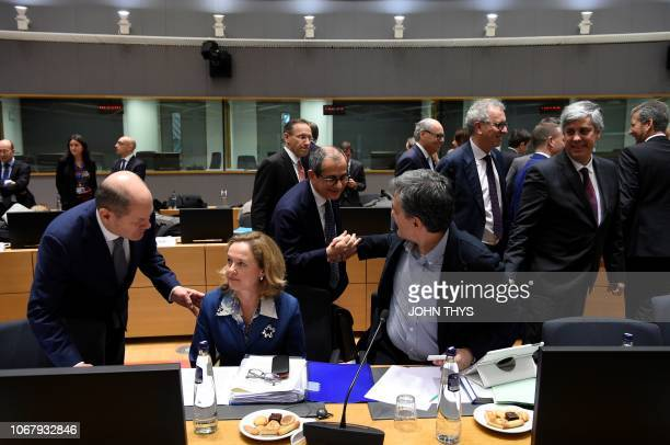Italian Minister for Economy and Finance Giovanni Tria shakes hand with Greek Finance Minister Euclid Tsakalotos as German Finance Minister Olaf...