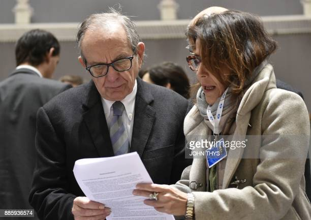 Italian Minister of Economy and Finance Pier Carlo Padoan talks with an advisor prior to an Economic and Financial Affairs meeting at the EU...