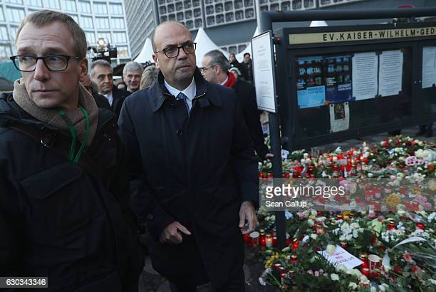 Italian Minister of Foreign Affairs Angelino Alfano walks past a makeshift memorial of flowers and candles left by mourners near the site where two...