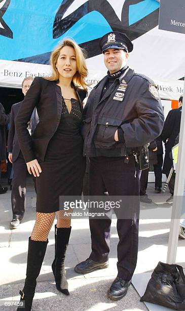 Italian model and entertainer Jo Squillo poses with a New York City police officer at a fashion show February 13 2002 in New York City