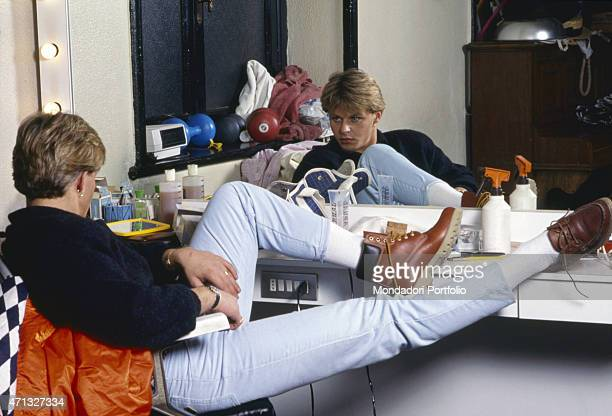 Italian model and frontman of musical project Den Harrow sitting with raised legs in his dressing room and looking at himself in the mirror Italy 1986