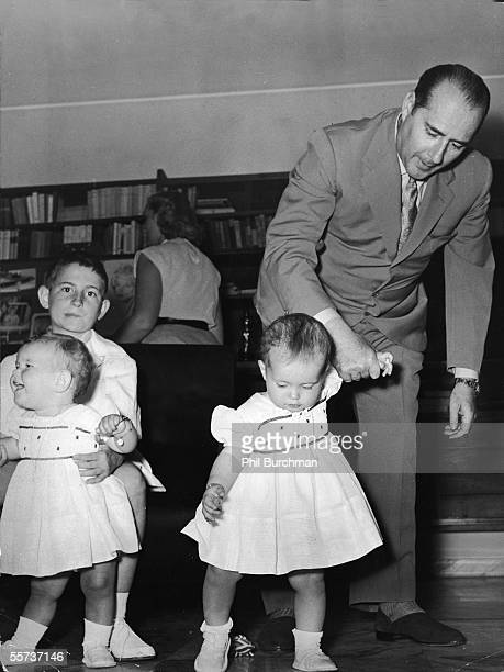 Italian motion picture director Roberto Rossellini holds the hand of one of his twin daughters as his son Robertino holds his other sister mid 1950s