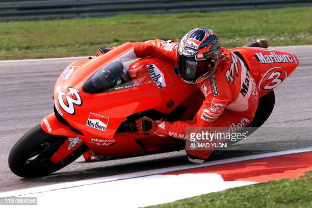 Italian MotoGP rider Max Biaggi leans his Marlboro Yamaha into a corner of the Sepang International Circuit during the first practice session of the...