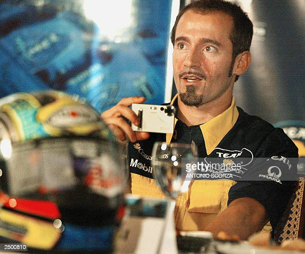 Italian MotoGP rider Maximiliano Biaggi takes a snapshot of the journalists 16 September 2003 during a HondaPons team press conference in Rio de...