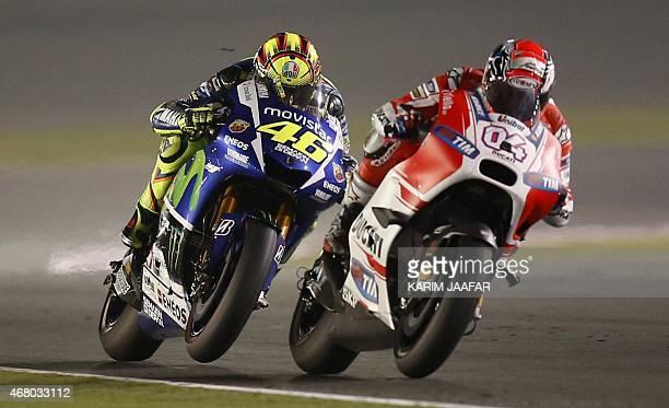 Italian MotoGP rider Valentino Rossi of the Movistar Yamaha team races with Andrea Dovizioso of Italy during the MotoGP race of the Qatar Grand Prix...