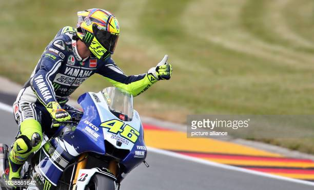 Italian MotoGP rider Valentino Rossi of the Yamaha Factory Racing team waves after the qualifying session held at the Sachsenring race track near...