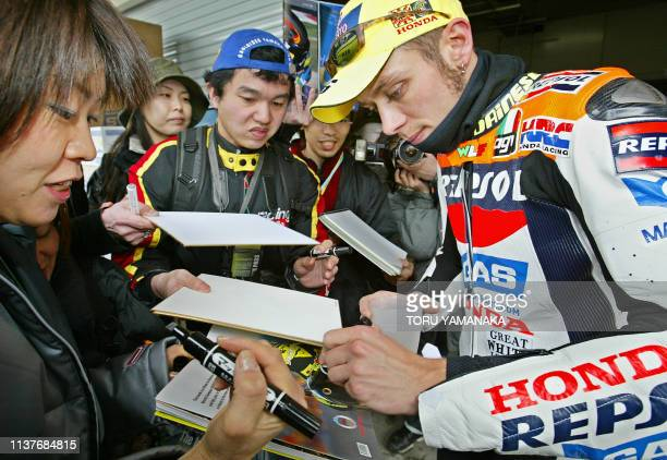 Italian MotoGP world champion Valentino Rossi signs autographs to Japanese fans after a free practice session for the motorcycle Grand Prix of Japan...
