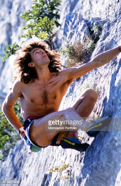 Italian mountain climber Manolo climbing a rock face bare chested Italy 1992