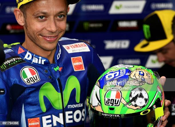 Italian Movistar Yamaha rider Valentino Rossi presents his new helmet dedicated to AS Roma football star Francesco Totti and late moto racer Nicky...