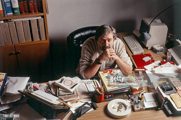 Italian musician, singer-songwriter and writer Francesco Guccini sitting at his desk. Among the books, there's the Donald Duck comic. Italy, 1988.