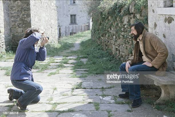 Italian musician singersongwriter and writer Francesco Guccini sitting on a stone bench and being photographed Pavana 1980