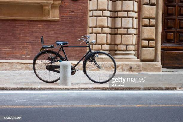 Italian old-style bicycles leaning against a wall in the historic centre  of Bologna