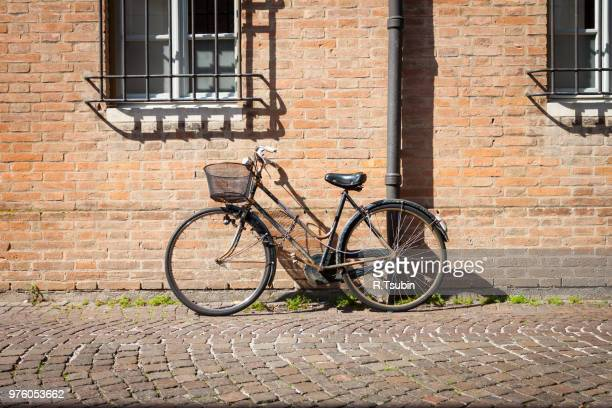 Italian old-style bicycles leaning against a wall in the historic center of Ferrara