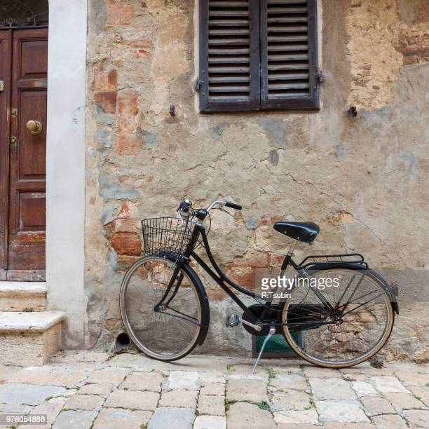 Italian old-style bicycles leaning against a wall in the historic centre of Ferrara