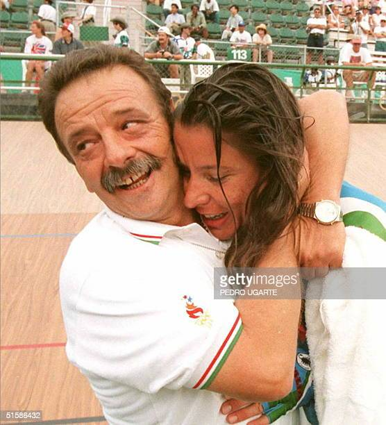 Italian Olympic cycling team coach Sandro Callari hugs Italian Antonella Bellutti after she set the best time in women's individual pursuit...