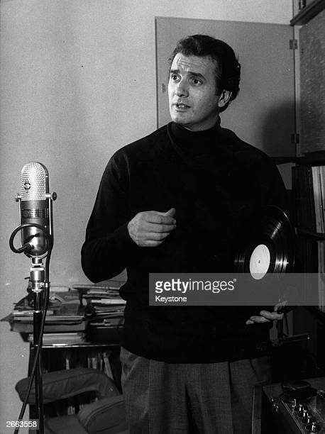 Italian opera singer Franco Corelli holding a record in front of an old fashioned microphone at his home in Milan, 9th December 1963.