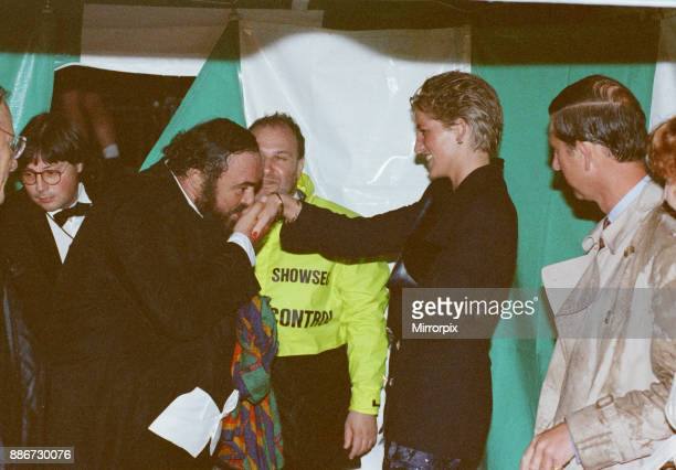 Italian opera singer Luciano Pavarotti kisses the hand of Princess Diana as Prince Charles looks on after the rain soaked Pavarotti in the Park...