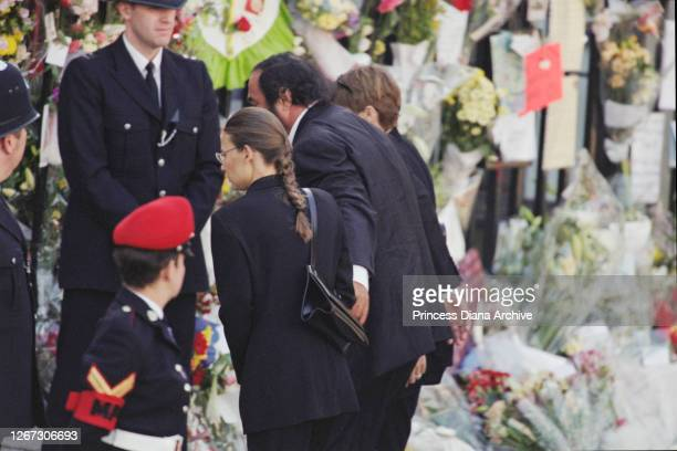 Italian operatic tenor Luciano Pavarotti and his partner Nicoletta Mantovani reading messages of condolence on their arrival at the funeral service...