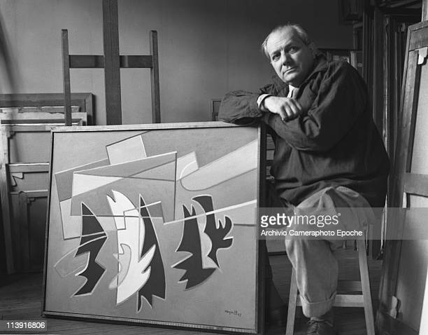 Italian painter Alberto Magnelli wearing corduroy trousers and a dark shirt in his parisian studio sitting on a chair next to one of his abstract...