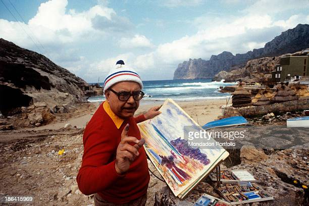 Italian painter Aligi Sassu shows some of his landscapes on a rocky beach he's wearing a wool cap and winter clothes Cala San Vicente Spain May 1982
