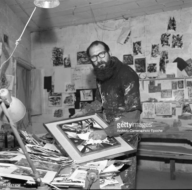 Italian painter Emilio Vedova cleaning a frame glass in his studio wearing a paintstained shirt and glasses surrounded by drawings and sketches...