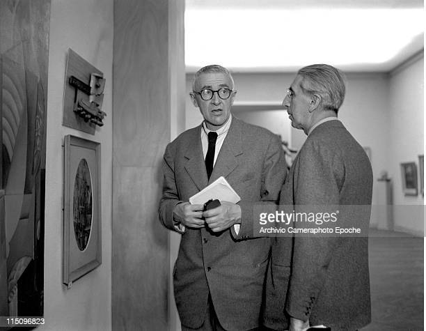 Italian painter Giorgio Morandi wearing a suit and glasses holding papers and standing with Longhi in front of some paintings Art Biennale Venice 1948