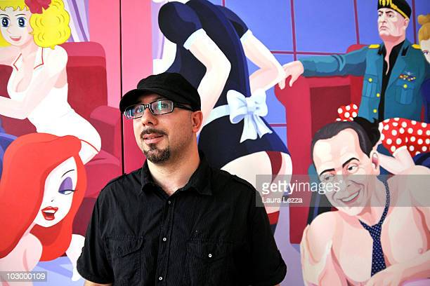 Italian painter Giuseppe Veneziano poses next to a detail of his painting 'Novecento' at Palazzo Panichi which is staging his latest major exhibition...