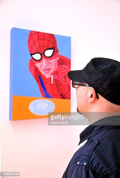 Italian painter Giuseppe Veneziano poses next to his painting 'Superspider cocaine' at Palazzo Panichi which is staging his latest major exhibition...