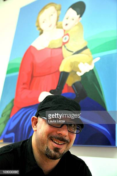 Italian painter Giuseppe Veneziano poses next to his painting 'La Madonna del terzo Reich' at Palazzo Panichi which is staging his latest major...
