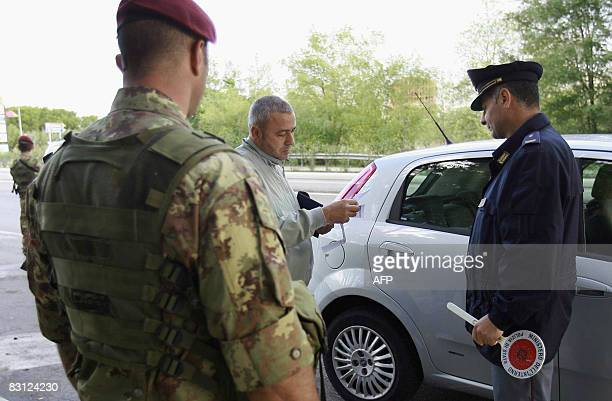 Italian paratroopers of the Folgore corp and a policeman check a car at a checkpoint in Casal di Principe near Caserta southern Italy on October 4...